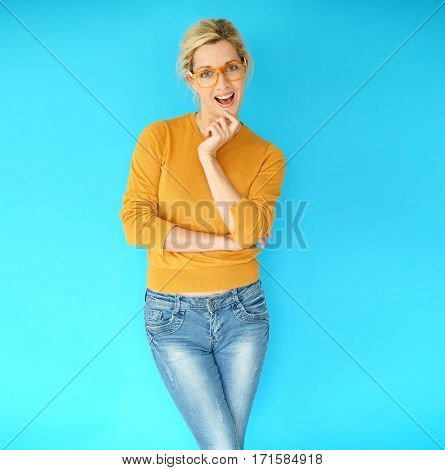 Blond woman with eyeglasses standing in front of blue background, isolated
