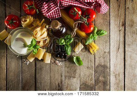 Tasty Colorful Fresh Italian Food Concept with Various Pasta Spaghetti Cheese Mozzarella Fresh Basil Tomatoes Olive Oil Spices. Top View. Cooking Concept. Place for Text.