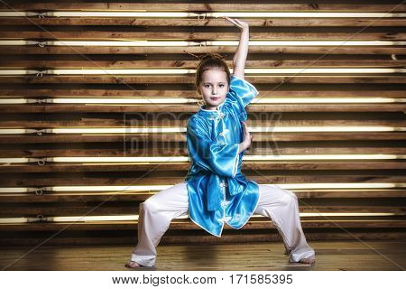 Pretty Little Girl In The Room In Sportswear For Martial Arts Is Wushu