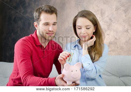 Young couple saves into piggybank. savings money couple piggybank home budget marriage cost concept