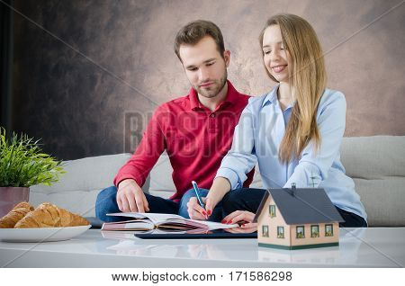 Young couple budget planning for own home. couple saving home marriage planning budget finance concept