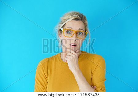 Portrait of blond woman with eyeglasses being astonished, isolated