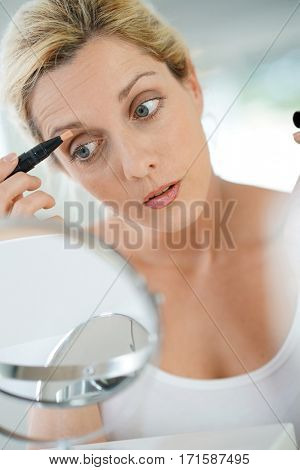 Middle-aged blond woman putting eye concealer in front of mirror
