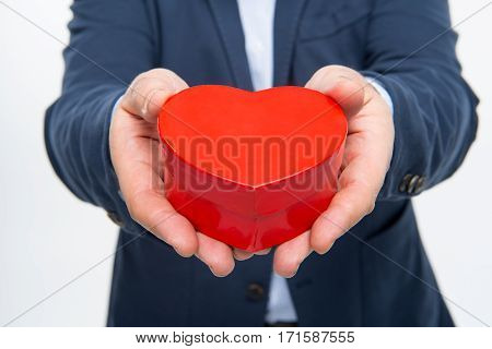 Close-up partial view of man holding red heart shaped gift box