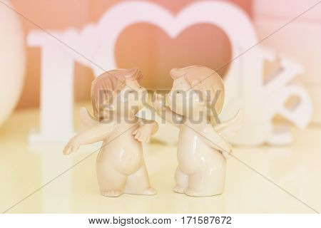 Two angels with white wooden letters forming word LOVE on background
