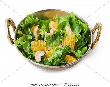 Vegan and vegetarian dish, fresh vegetable and fruit salad in copper bowl closeup isolated on white background. Indian restaurant healthy meal, lettuce, cashew and orange mix. Eastern local food.