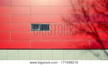 The front facade of a modern building of gray and red panels wih small window. Shadows of the trees on the facade of the building. Architectural background.