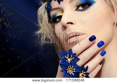 Blue manicure and makeup with gold eye shadow and bright lipstick on the woman in closeup.