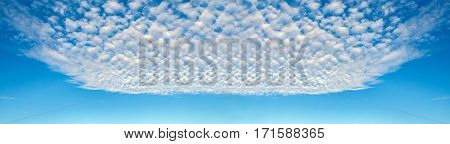Panorama of blue sky and shapes of flying clouds. Heavenly background in a highly patterned top. Free space atmospheric flight and freedom.