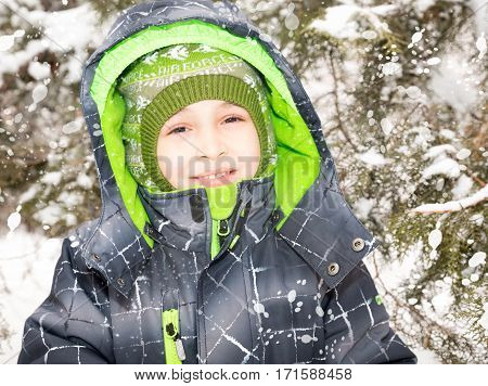 Close up portrait of adorable happy little boy grinning happily at the camera on a sunny winter's day
