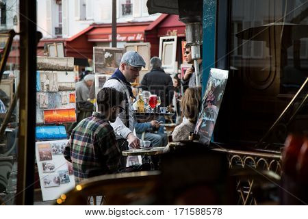 PARIS, FRANCE - MARCH 8, 2015:  Waiter serving the guests at table in typical  cafe on Place du Tertre, Montmartre hill.