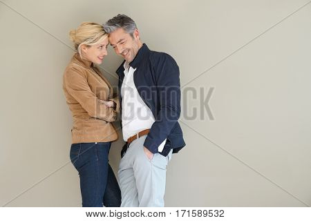 Middle-aged couple standing on grey background, isolated