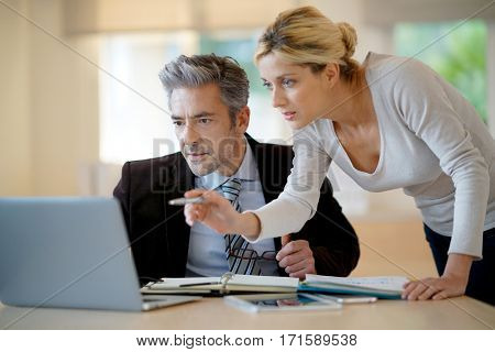 Notary in office working on agenda with assistant