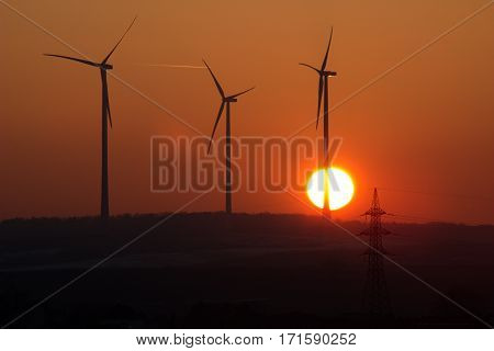 three wind power plants at sunset and a pillar of high voltage power lines