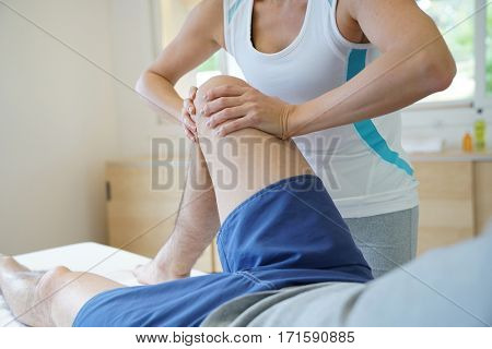 Physiotherapist massaging athlete in physical recovery