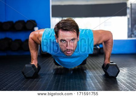Portrait of serious athlete doing push-ups with dumbbells in gym