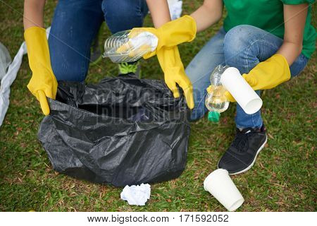 Young woman holding black bin bag while her friend putting plastic household waste into it, close-up shot