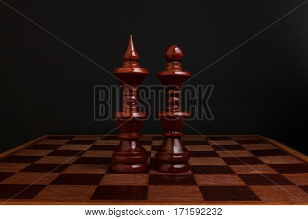 Chess. Black King and Queen on wood board. The most powerful figures. Set of chess figures.