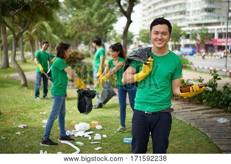 Portrait of young Vietnamese man looking at camera with toothy smile while holding glass bottles and bin bag, his friends standing behind and collecting garbage