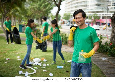 Smiling middle-aged Asian man wearing rubber gloves distracted for second from collecting garbage in order to pose for photography