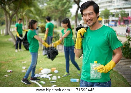 Portrait of middle-aged man with wide smile standing with plastic container in hand, his male and female friends picking up garbage in green park