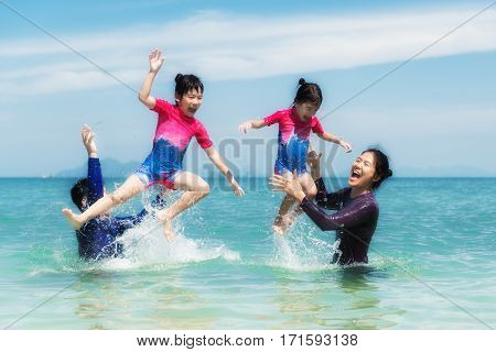 Happy Asian family playing in the ocean and splashing water in Phuket Thailand. Asian family tourists on summer vacation on a tropical island.