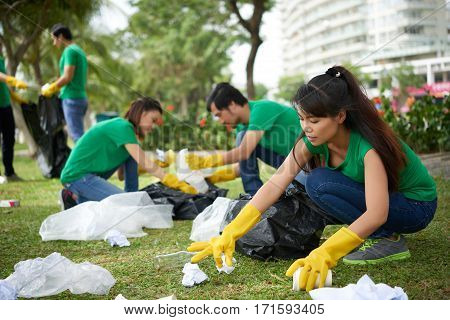 Profile view of pretty Asian woman with long hair sitting on haunches and collecting trash lying on park lawn