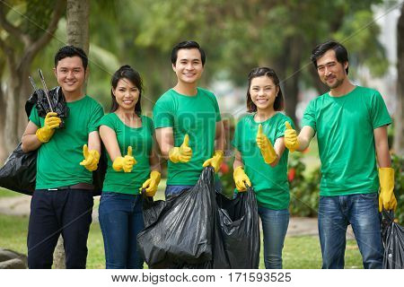 Full-length portrait of cheerful Asian environmental activists standing in row with thumbs up and holding full bin bags