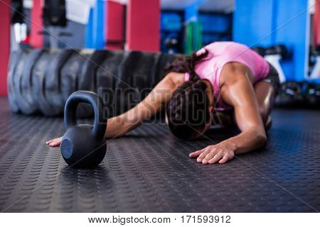 Fit female athlete exercising while kneeling in gym