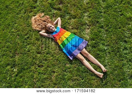Young girl on lying on freshly mowed lawn in rainbow colored dress
