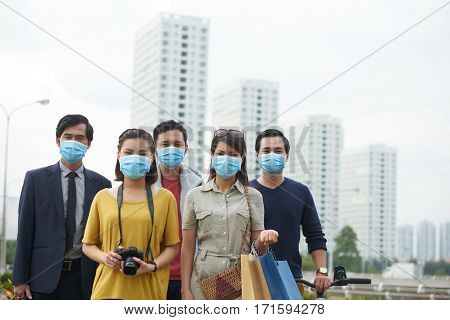 Waist-up portrait of Asian friends in protective masks looking at camera while standing against modern skyscrapers