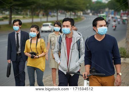 Asian people of different ages walking along street and protected themselves from flue with help of medical masks