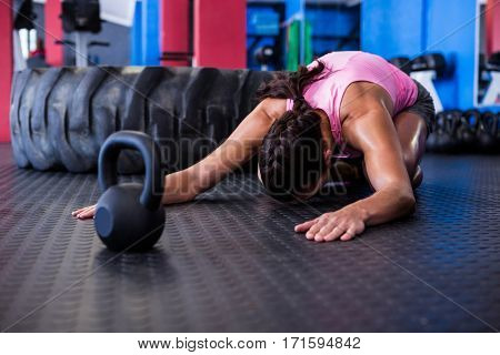 Female athlete exercising while kneeling in gym