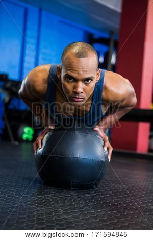 Portrait of young man using exercise ball in gym