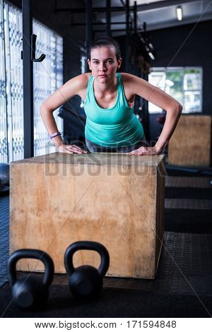 Portrait of young athlete using wooden cube while exercising in gym