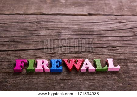 firewall word made from colored wooden letters on an old table. Concept