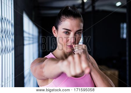 Portrait of confident athlete punching in gym