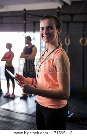 Portrait of happy female fitness instructor holding clipboard while standing in gym