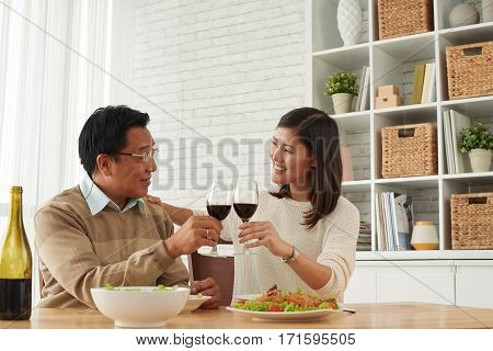 Senior Asian man and his young daughter celebrating Fathers Day together: they holding glasses of wine in hands and clinking them together