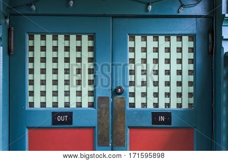 Elaborate Swinging Blue and Red Doors with In and Out Signs