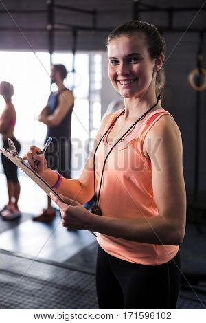 Portrait of cheerful female fitness instructor holding clipboard while standing in gym