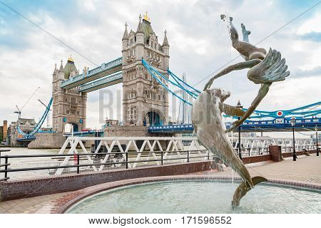 LONDON ENGLAND - JUNE 26 2013: View of the Tower Bridge with David Wynnes's statue of Girl with Dolphin from St Katharine docks. The Shard Tower in background