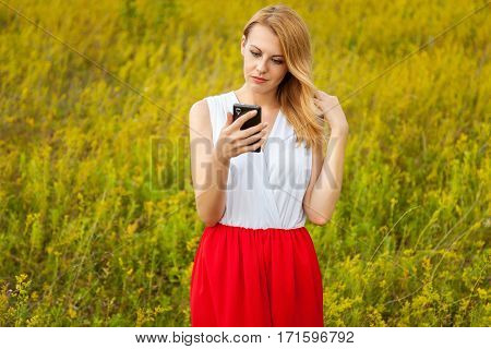 Blonde with the phone. The beautiful blonde girl in white-red dress watches her mobile phone in the green field. The girl in the field with the phone the girl makes self the girl with the tablet a girl with headphones girl listening to music