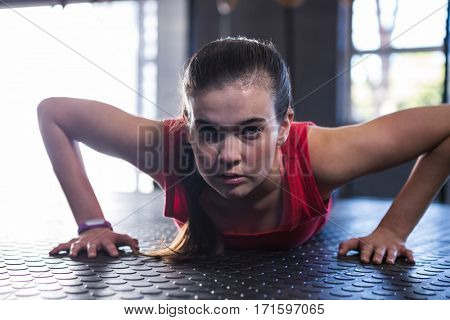Portrait of sporty athlete doing push-ups while exercising in gym