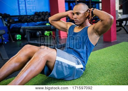Young male athlete with hands behind back while exercising in gym