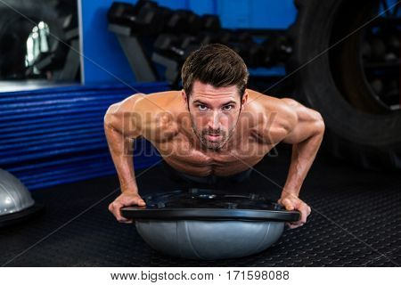 Portrait of determined male athlete exercising with BOSU ball in fitness studio