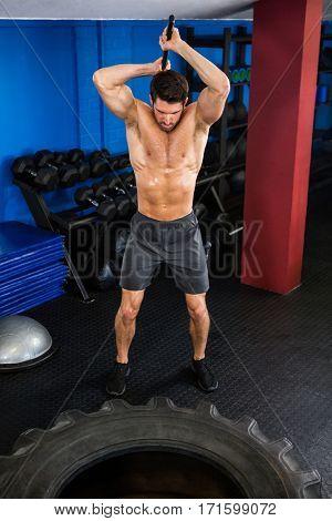 Shirtless man doing sledgehammer swing exercise in fitness studio
