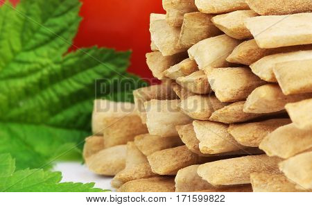 Crispy crunchy wheat breadsticks close-up on a background of tomato and green leaf.