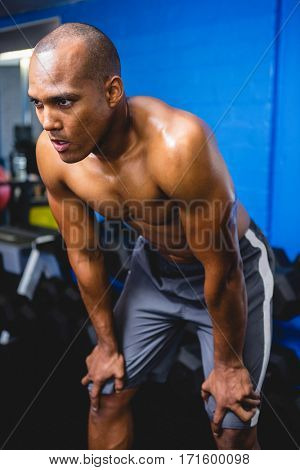 Shirtless athlete bending with hands on knee in gym