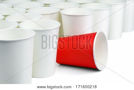 One different unique red paper cup among white ordinary cups lined up diagonally. Concept.
